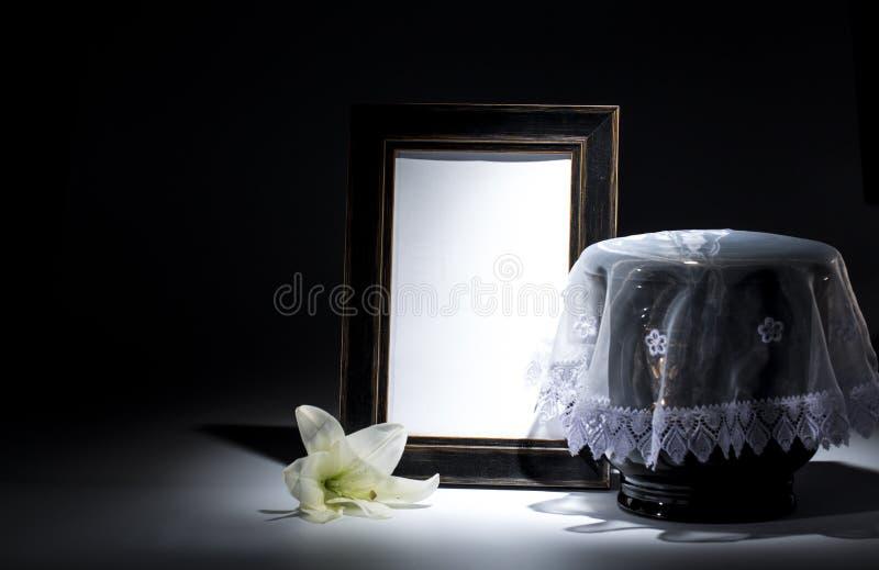 Czarny ewangelicki łzawica z pustą opłakuje ramą i kwiatem, fotografia stock