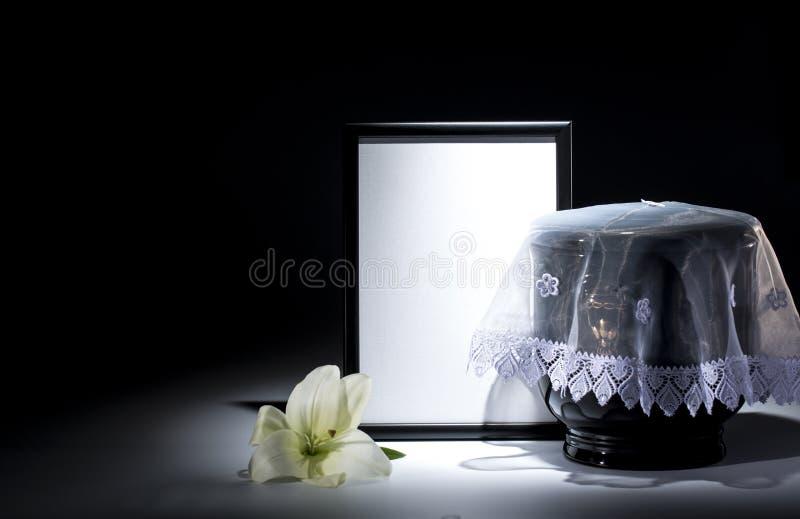Czarny ewangelicki łzawica z pustą opłakuje ramą i kwiatem, obraz royalty free