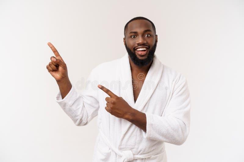 Czarny facet jest ubranym bathrobe wskazuje palec z niespodzianką i szczęśliwą emocją Odizolowywający nad whtie tłem zdjęcie stock