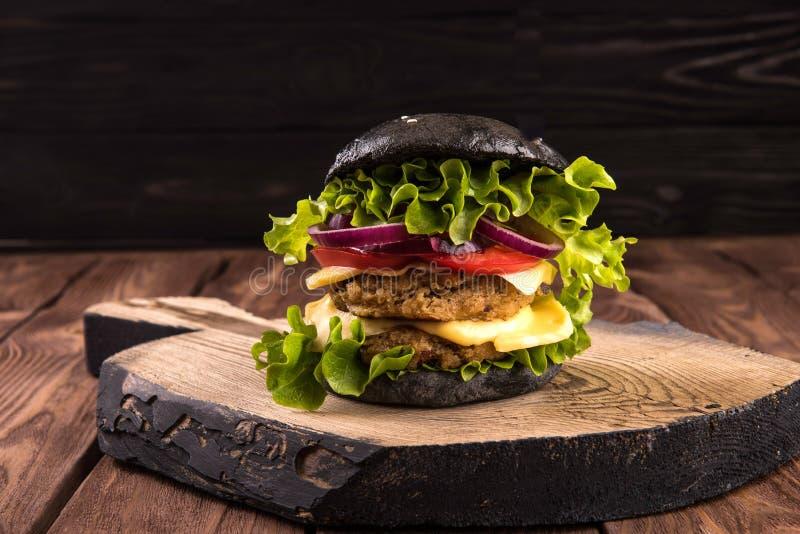 Czarny hamburger na desce na pięknym czarnym drewnianym nieociosanym tle obraz stock