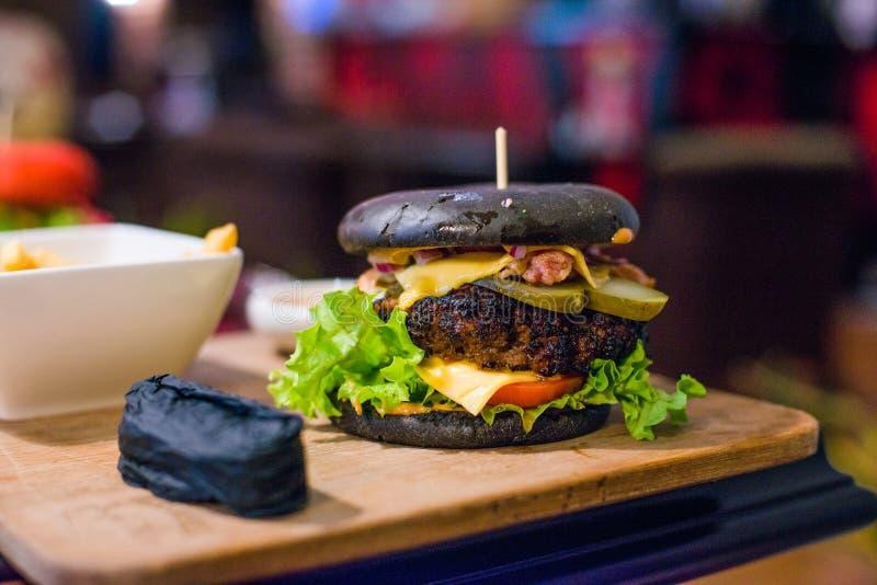 Czarny hamburger na drewnianej desce Stonowany obrazek zdjęcie stock