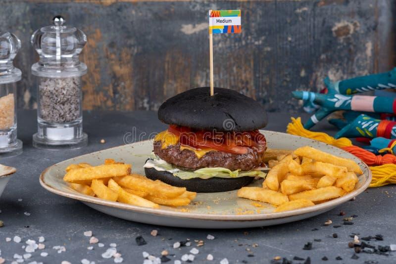 Czarny hamburger z mięsnym pasztecikiem, ser, pomidory, majonez, francuz smaży w papierze Zmroku kamienny t?o Nowożytny post obraz royalty free