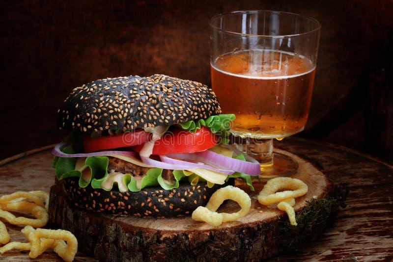 Czarny hamburger z piwnymi i cebulkowymi pierścionkami zdjęcia royalty free