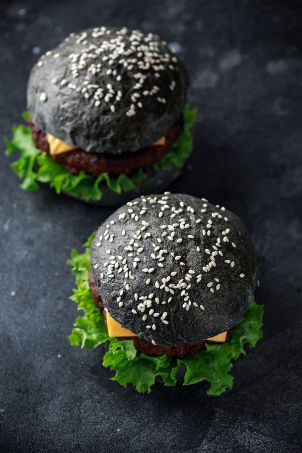 Czarny hamburger z sera, wołowiny i Zielonej sałatki liśćmi, cheeseburger domowej roboty obrazy royalty free