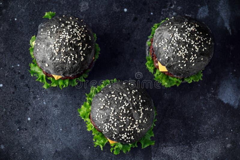 Czarny hamburger z sera, wołowiny i Zielonej sałatki liśćmi, cheeseburger domowej roboty fotografia royalty free