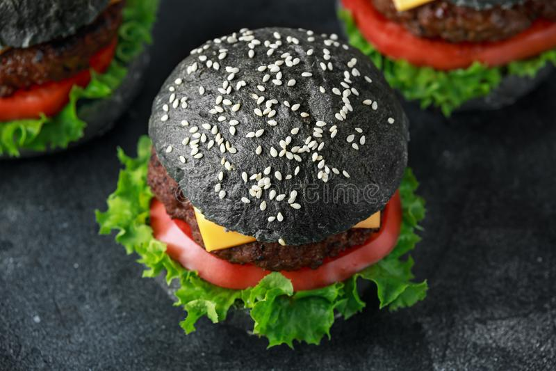 Czarny hamburger z serem, wołowiną, pomidorami i Zielonej sałatki liśćmi, cheeseburger domowej roboty zdjęcia royalty free