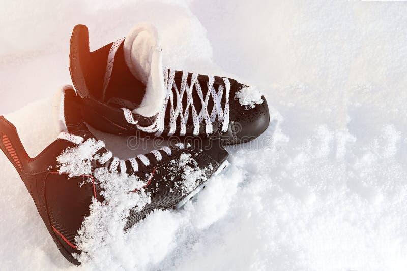 Czarny hokej jeździć na łyżwach lying on the beach w jaskrawym słońcu i śniegu obraz stock