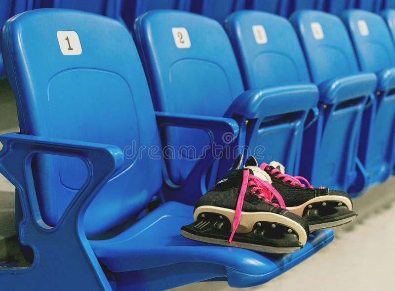 Czarny hokej jeździć na łyżwach z świstów bootlaces na krześle na pustym stadium Rzędy numerację fotografia royalty free