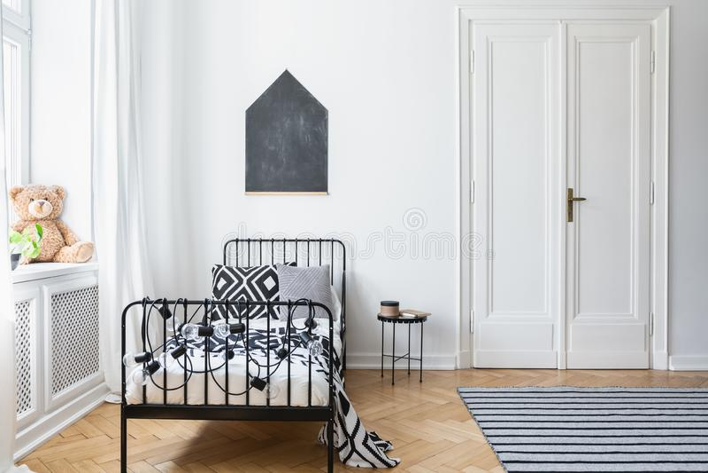 Czarny i biały łóżko w nastolatka ` s sypialni wnętrzu z mokietu plakatem na ścianie i zabawką zdjęcie royalty free