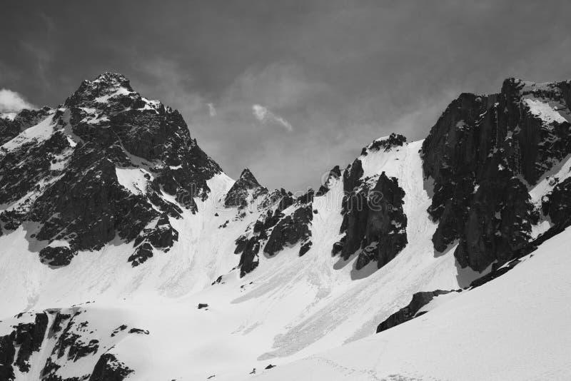 Czarny i biały śnieg zakrywał góry z śladami od lawin w zimie fotografia stock