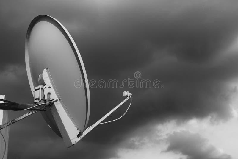 Czarny i biały antena satelitarna na dachu przeciw chmurnemu niebu obrazy royalty free