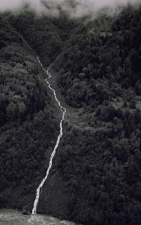 Czarny i biały fotografia góry rzeczny spływanie zestrzela wąwóz na tle zieleniste góry i chmury fotografia royalty free