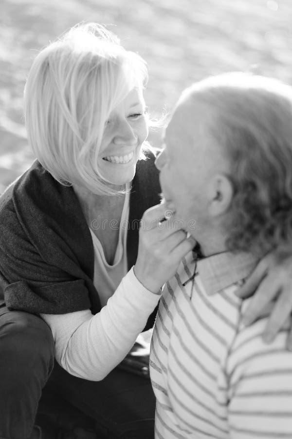 Czarny i biały fotografia starszego żony przytulenia starszy mąż i obsiadanie na piasku wyrzucać na brzeg zdjęcia royalty free
