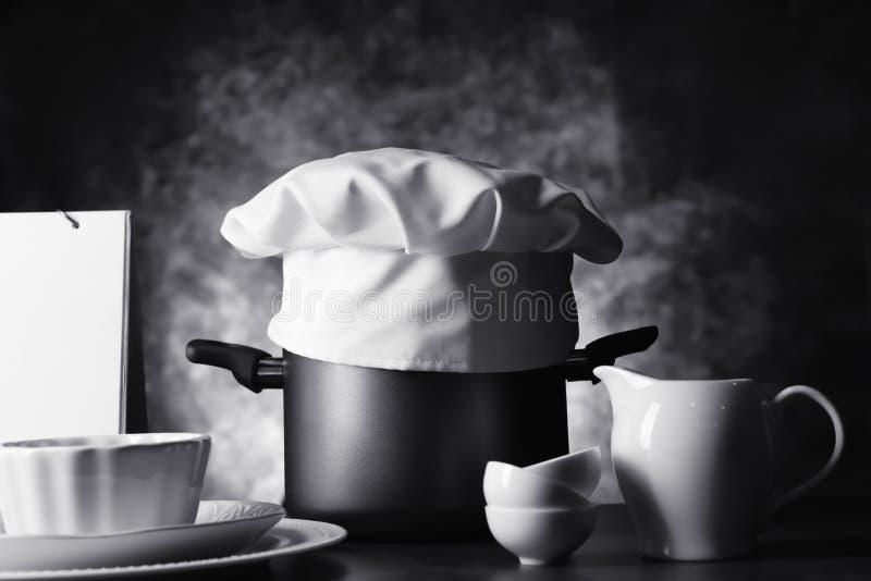Czarny i biały fotografia szef kuchni, s kapelusz z kitchenware na ciemnym tle « obraz royalty free