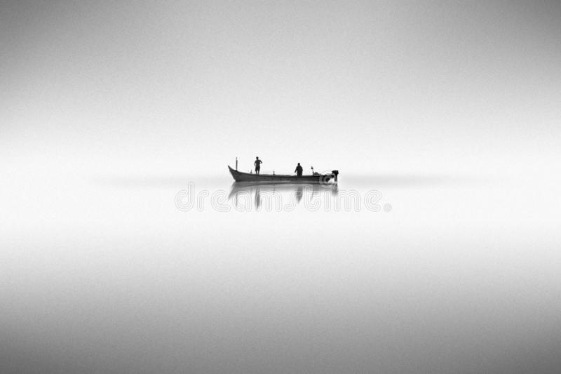 Czarny i biały fotografia z łodzią na wodzie w mgle zdjęcie royalty free