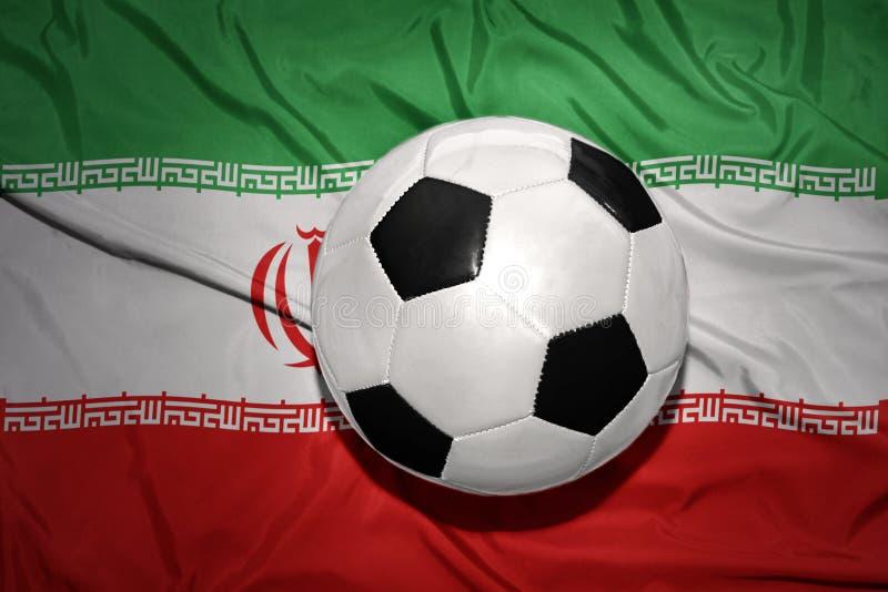 Czarny i biały futbolowa piłka na flaga państowowa Iran zdjęcia stock