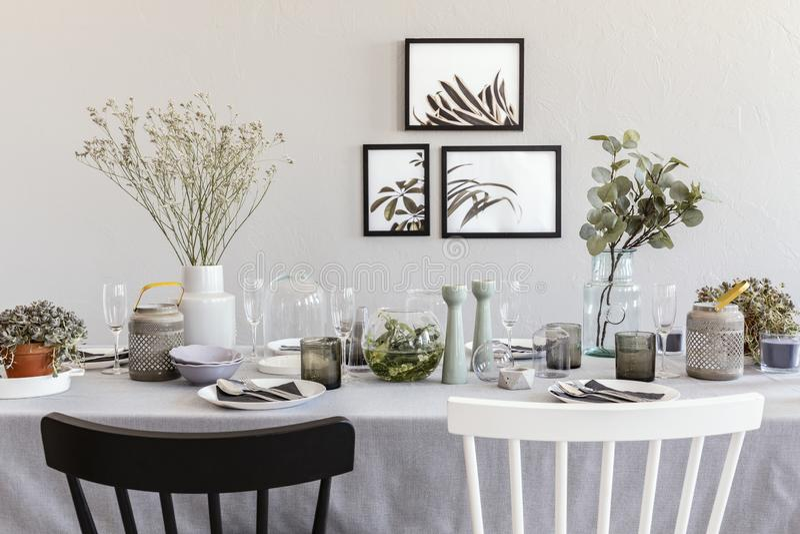 Czarny i biały krzesło przy stołem z tableware w popielatym jadalni wnętrzu z plakatami zdjęcia royalty free