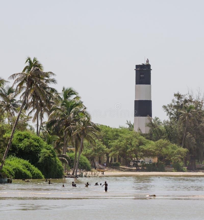 Czarny i biały latarnia morska z palmami, drzewami i dopłynięcie miejscowymi przy morzem, Ndiebene, Senegal fotografia stock