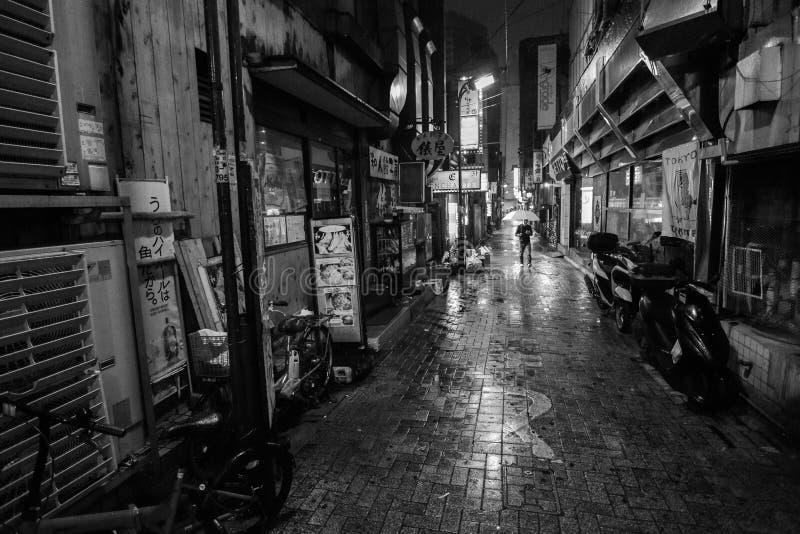 Czarny i biały mężczyzna z parasolowym odprowadzenie puszkiem osamotniony alleyway na dżdżystej nocy w Tokio obraz stock