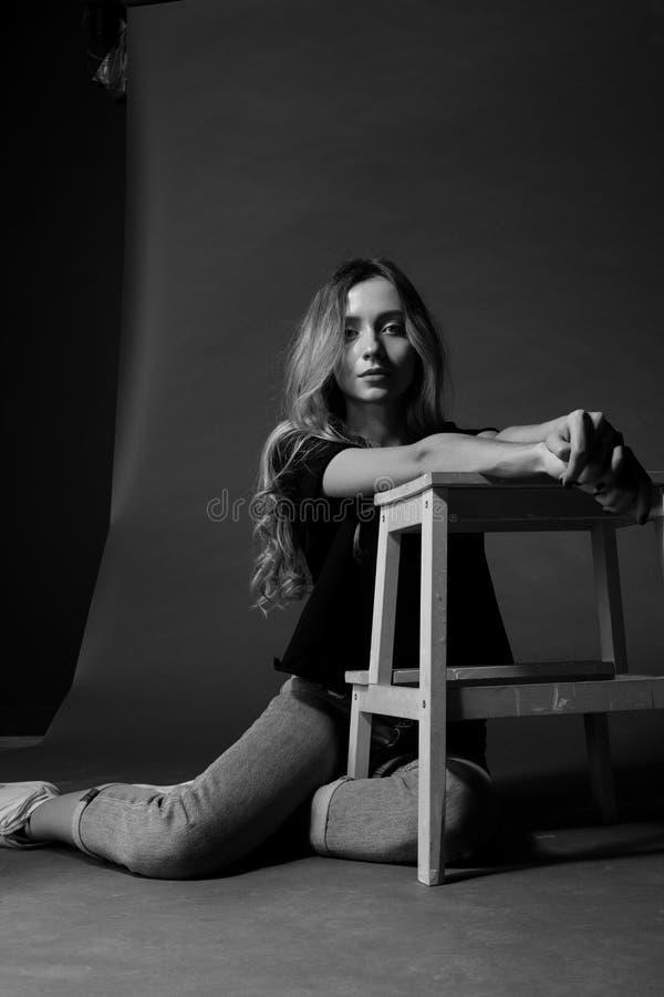 Czarny i biały portret blondynki dziewczyna siedzi na podłoga opiera na krześle przeciw ciemnemu tłu w koszulce i cajgach, model fotografia stock