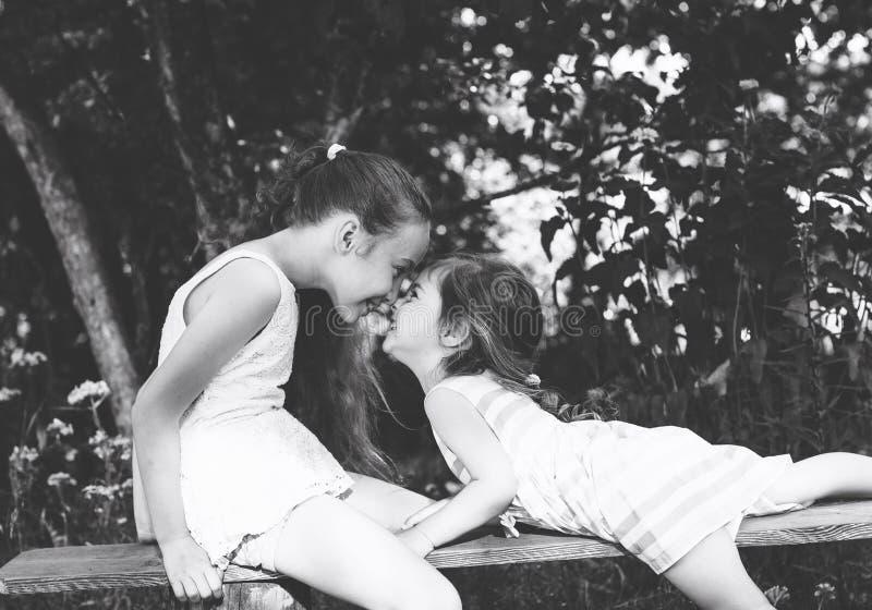 Czarny i biały portret Dwa małych dziewczynek ono uśmiecha się ślicznego pl i zdjęcie stock