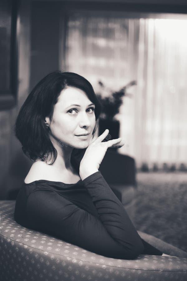 Czarny i biały portret kobieta siedzi indoors zdjęcia stock