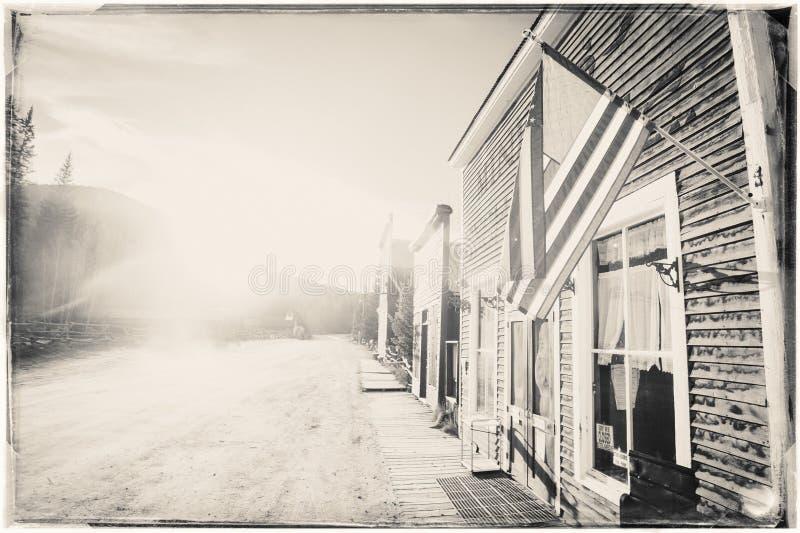 Czarny I Biały Sepiowa rocznik fotografia Starzy Zachodni Drewniani budynki z flagą zlani stany fotografia stock