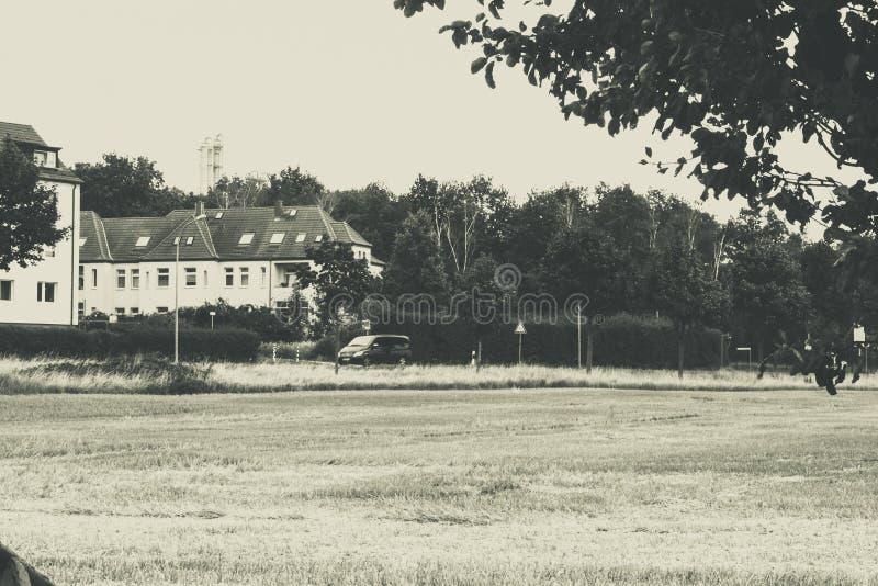 Czarny i biały stonowana fotografia z polem i domami zdjęcie stock
