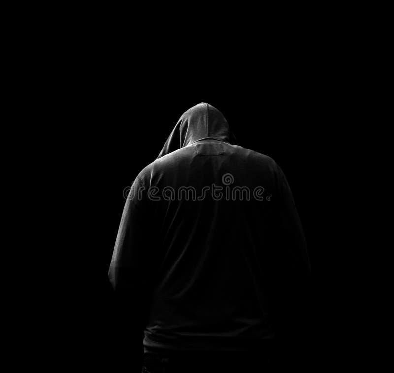 Czarny i biały sylwetka kapturzasty mężczyzna odizolowywał na czarnym tle, który obracał daleko od, obrazy royalty free