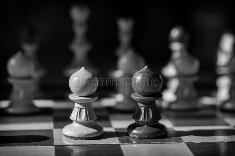Czarny i biały szachowi pionkowie stawiają czoło daleko fotografia stock