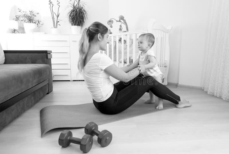 Czarny i biały wizerunek ćwiczy na podłoga z h szczęśliwa matka fotografia royalty free