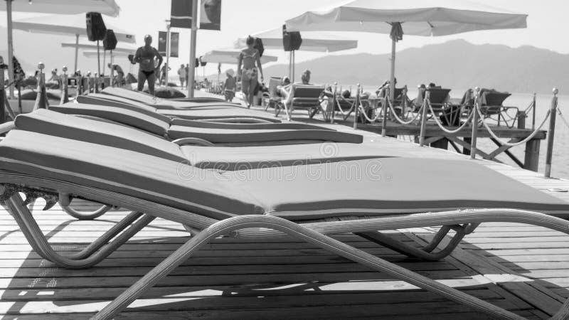 Czarny i biały wizerunek prosty rząd puści sunbeds na drewnianym molu obrazy royalty free