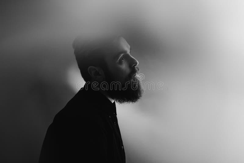 Czarny i bia?y fotografia portret elegancki m??czyzna w profilu z brod? ubiera? w czarnej koszula w mgle zdjęcia stock