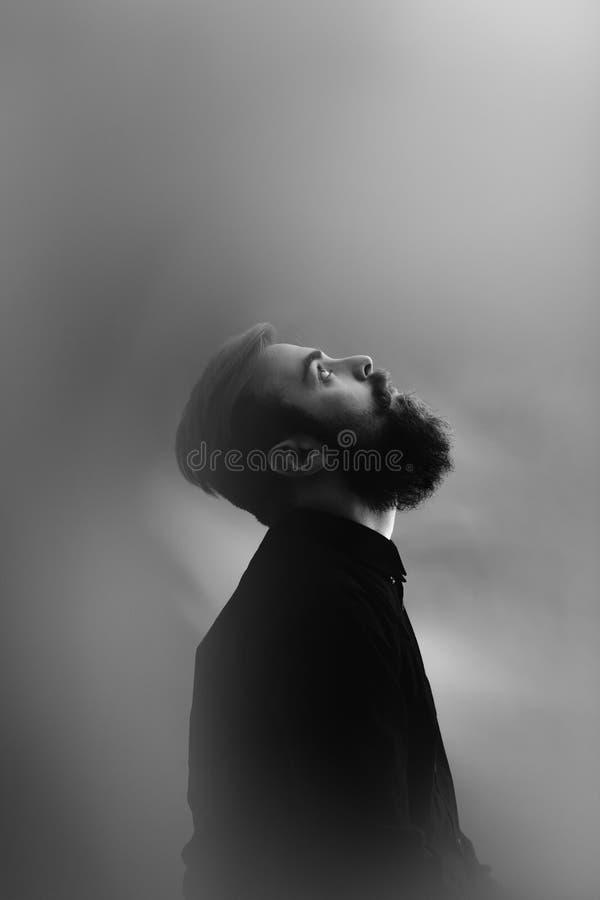 Czarny i bia?y fotografia portret elegancki m??czyzna w profilu z brod? ubiera? w czarnej koszula w mgle fotografia royalty free