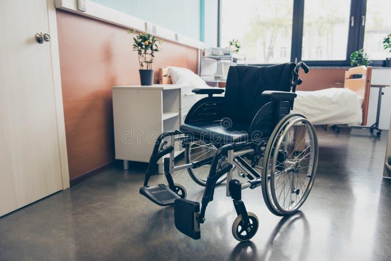 czarny koła krzesło w pustym izbowym oddziale szpital Zamyka w górę fotografii, łóżko jest na tle, biała drzwi medycyna zdjęcie stock