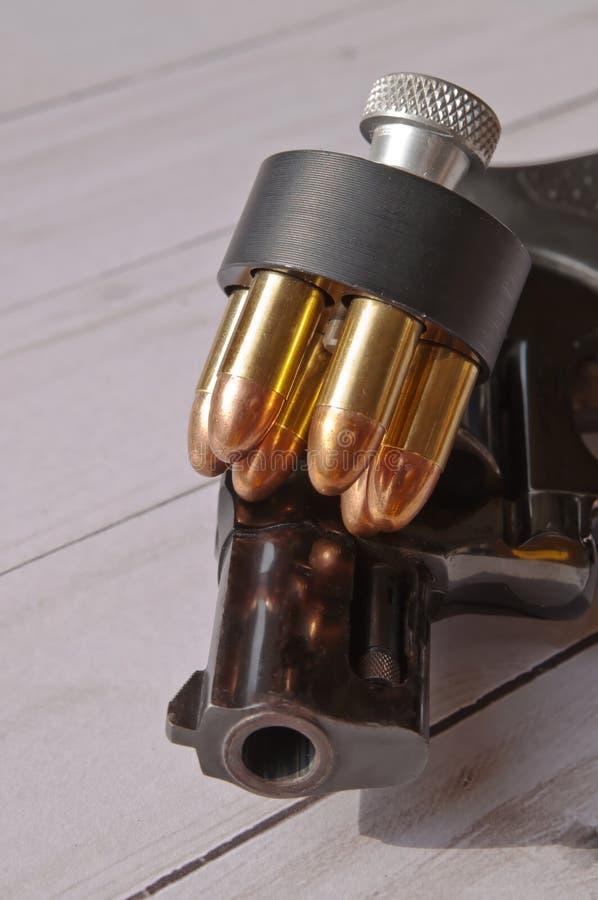 Czarny kolt z ładownym prędkość ładowaczem z 38 specjalnymi pełnymi metal kurtki pociskami na górze go zdjęcia royalty free