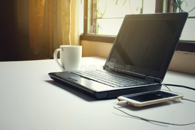 Czarny komputerowy laptopu notatnika komputer osobisty na pracującym stole z białą filiżanką i mądrze telefonem w biurze zdjęcia stock