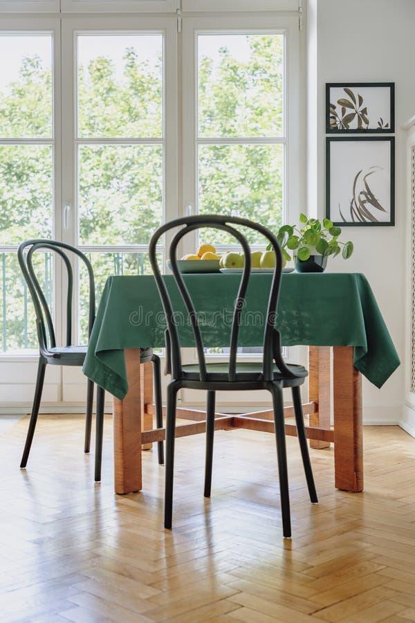 Czarny krzesło obok stołu z zielonym płótnem w jadalni wnętrzu Balkonowy okno w tle zdjęcia stock