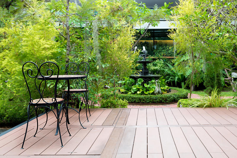 Czarny krzesło w drewnianym patiu przy zieleń ogródem z fontanną w domu obrazy stock