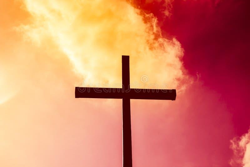 Czarny krzyż na tle czerwony i żółty płomienny niebo, od zdjęcie stock