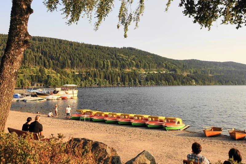 Czarny las, Jeziorna Titisee plaża z Do wynajęcia łodziami i turyści, obrazy royalty free