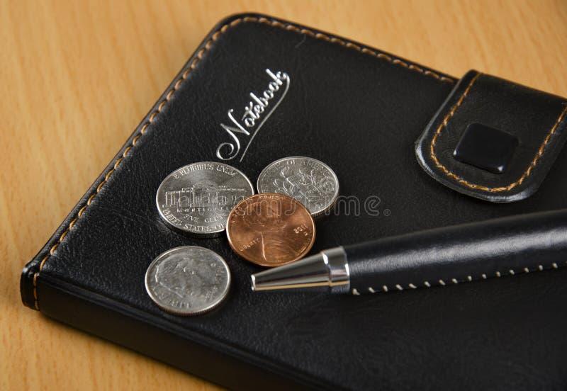 Czarny notatnik i USA monety fotografia stock