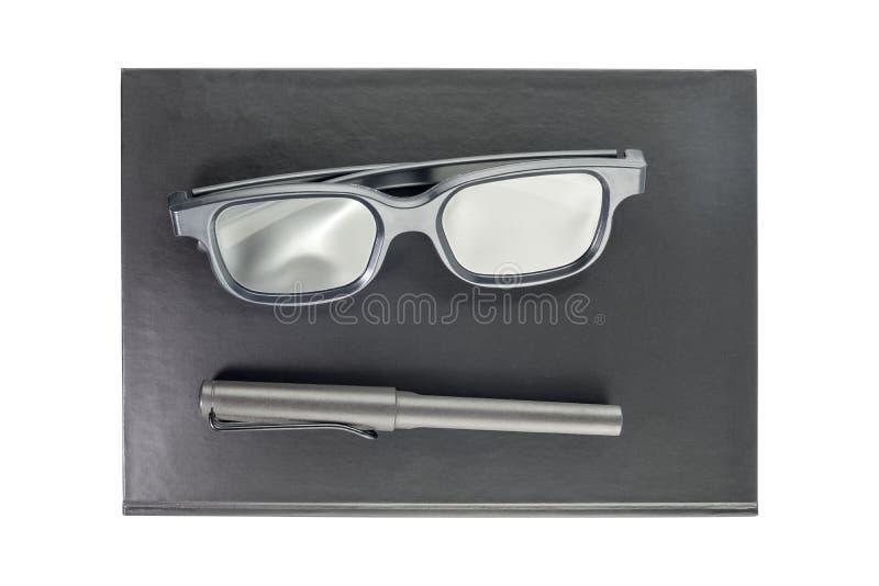 Czarny notatnik z szkłami i pióro nad odosobnionym na białym backg fotografia stock