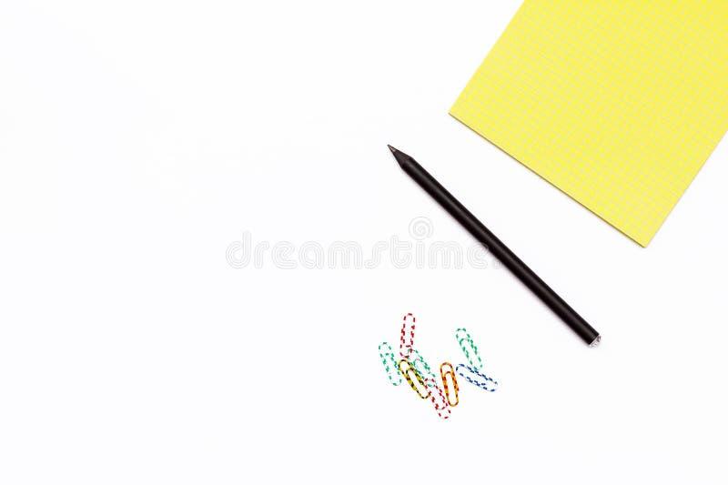 Czarny ołówek, barwione papierowe klamerki i żółty Notepad, Minimalny pojęcia desktop w biurze zdjęcia royalty free