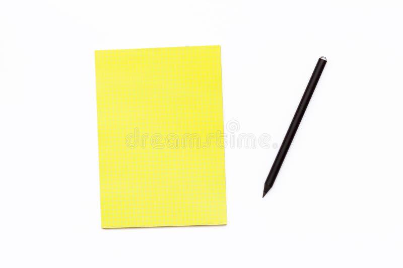 Czarny ołówek i żółty Notepad na białym tle Minimalnego biznesowego pojęcia biurowy biurko obraz stock