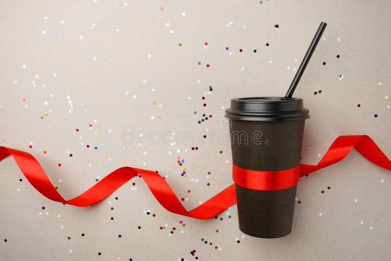 Czarny papierowy filiżanka kawy iść i czerwony jedwabniczy faborek na szarym tle z confetti, egzamin próbny w górę, elegancki świ fotografia royalty free