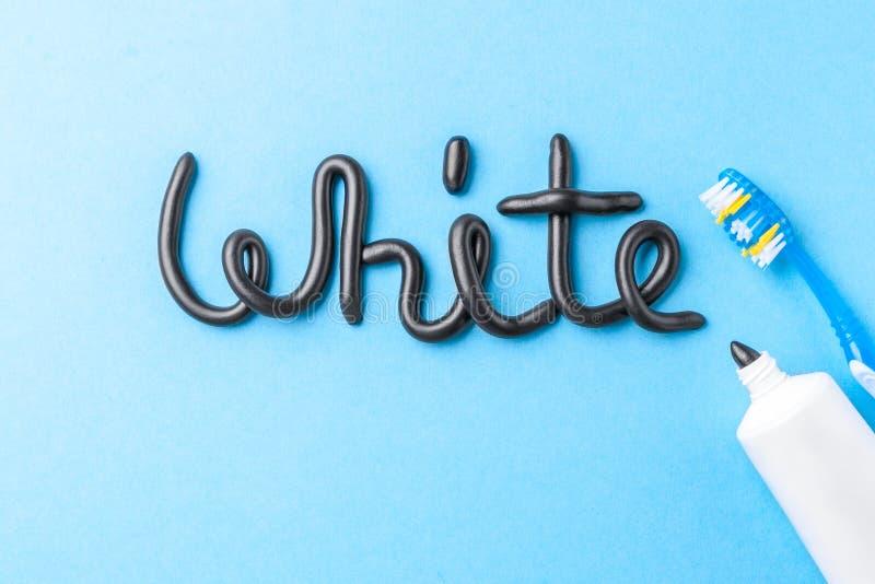 Czarny pasta do zębów od węgla drzewnego dla białych zębów Formułuje biel od pasta do zębów, tubki i toothbrush na błękicie czarn zdjęcie royalty free