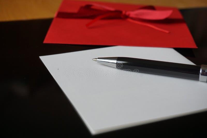 Czarny pióra writing zawiadomienia list z dekorującą czerwoną kopertą fotografia stock