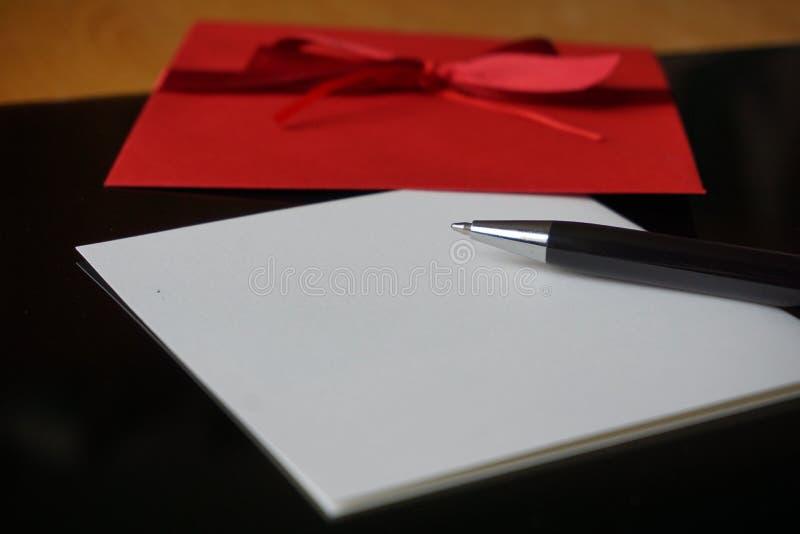 Czarny pióra writing zawiadomienia list z dekorującą czerwoną kopertą zdjęcia stock
