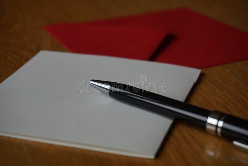 Czarny pióra writing zawiadomienia list z kopertą na drewnianym biurku zdjęcie stock